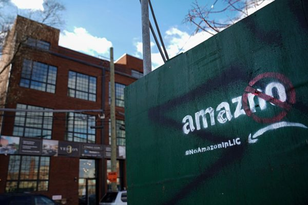 A protest message directed at Amazon is spray painted on a wall near a construction site in the Long Island City