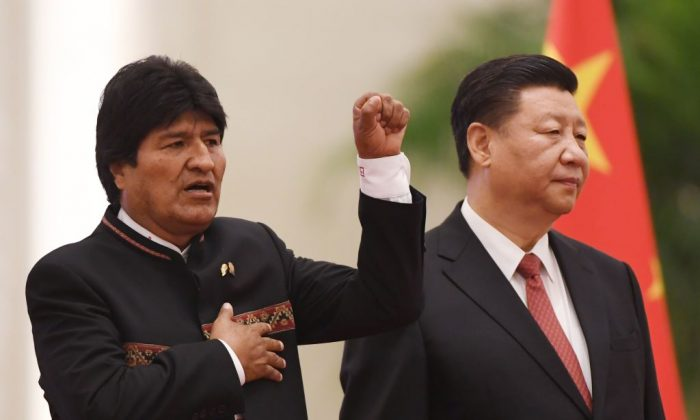 Bolivia's President Evo Morales (L) sings his national anthem as Chinese leader Xi Jinping (R) looks on during a welcome ceremony in the Great Hall of the People in Beijing on June 19, 2018. (Greg Baker/AFP/Getty Images)