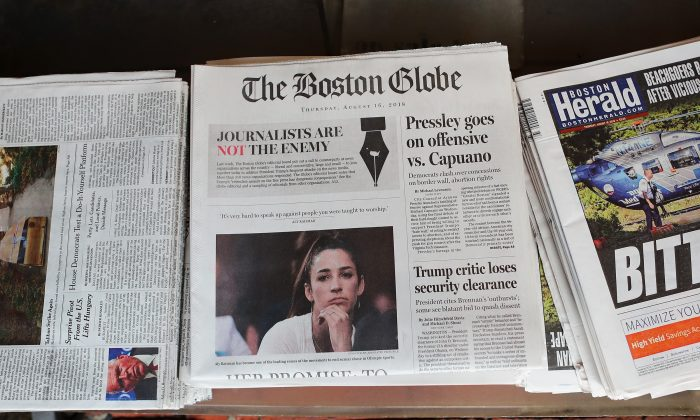 """The front page of the August 16, 2018 edition of the Boston Globe newspaper reads """"Journalists are Not the Enemy."""" (Tim Bradbury/Getty Images)"""