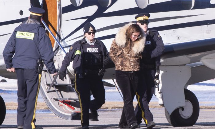 RCMP officers escort a female suspect in a money laundering network off an airplane in St-Hubert, Quebec, on Feb. 11, 2019. (The Canadian Press/Paul Chiasson)