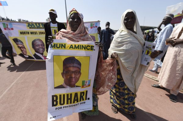 A supporter carries a banner depicting the candidate of the ruling All Progressives Congress (APC).