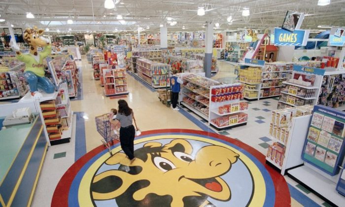 A woman pushes a shopping cart over a graphic of Toys R Us mascot Geoffrey the giraffe at the Toys R Us store in Raritan, N.J. on July 30, 1996. (AP Photo/Daniel Hulshizer, File)