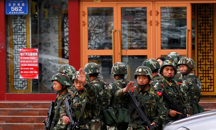 Paramilitary policemen gesture to stop a photographer from taking pictures as they stand guard after an explosives attack hit downtown Urumqi in the Xinjiang Uyghur Autonomous Region on May 23, 2014.  (Petar Kujundzic/Reuters)