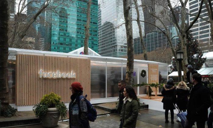 People walk by as the social network Facebook opens a pop-up kiosk for one day in Bryant Park in New York, Dec. 13, 2018, where it fields questions about its data-sharing practices and teach users how to understand its new privacy controls. (TIMOTHY A. CLARY/AFP/Getty Images)