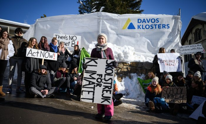 "Swedish youth climate activist Greta Thunberg (C) holds a placard next to students during a ""School strike for climate"" held on the sidelines of the World Economic Forum (WEF) annual meeting, on January 25, 2019 in Davos, eastern Switzerland. FABRICE COFFRINI/AFP/Getty Images"