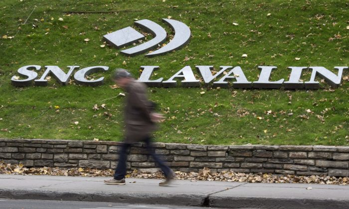 A man walks past the SNC-Lavalin Group Inc., headquarters. (Paul Chiasson/The Canadian Press)