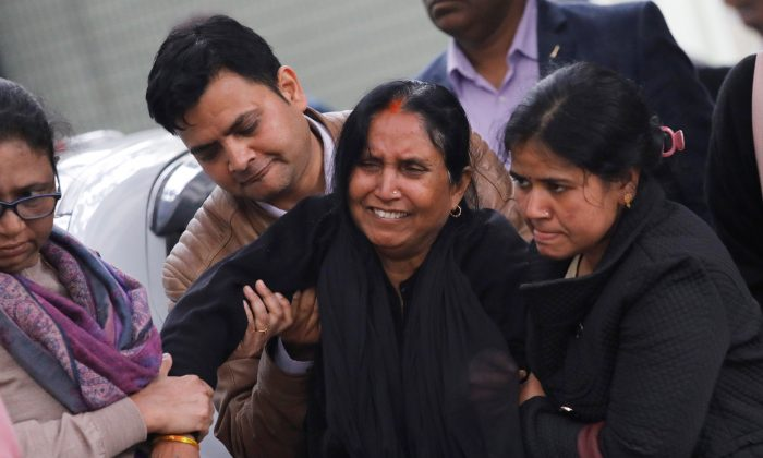 A woman cries as family members hold her while waiting outside a mortuary to receive the body of her relative, who was killed in a fire at a hotel in New Delhi, India, Feb. 12, 2019.(Anushree Fadnavis/Reuters)