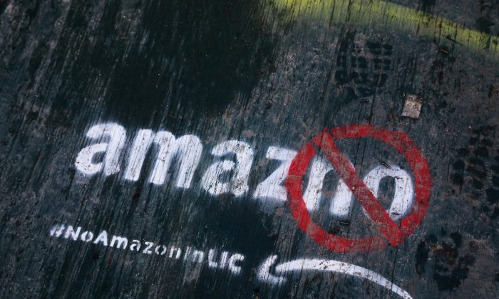 Graffiti painted on a sidewalk by someone opposed to the location of an Amazon headquarters in the Long Island City neighborhood in the Queens borough of New York, photo taken on Nov. 16, 2018. (AP Photo/Mark Lennihan, File)