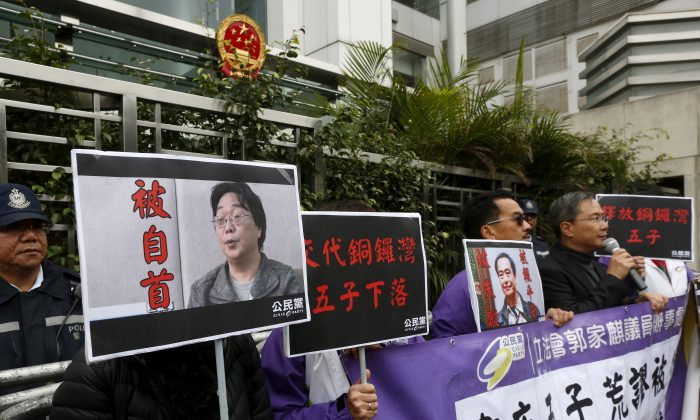 Members of the pro-democracy Civic Party carry a portrait of Gui Minhai (L) and Lee Bo during a protest outside the Chinese Liaison Office in Hong Kong on Jan. 19, 2016. (Bobby Yip/Reuters)