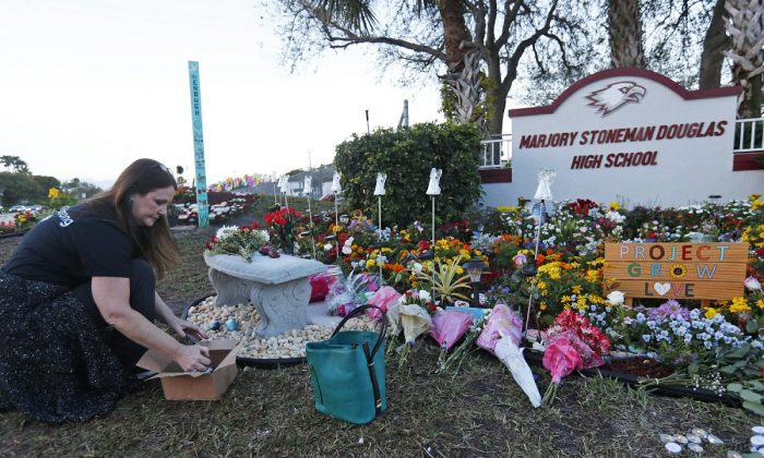 Suzanne Devine Clark, an art teacher at Deerfield Beach Elementary School, places painted stones at a memorial outside Marjory Stoneman Douglas High School during the anniversary of the school shooting, in Parkland, Fla., on Feb. 14, 2019.(Wilfredo Lee/AP Photo)