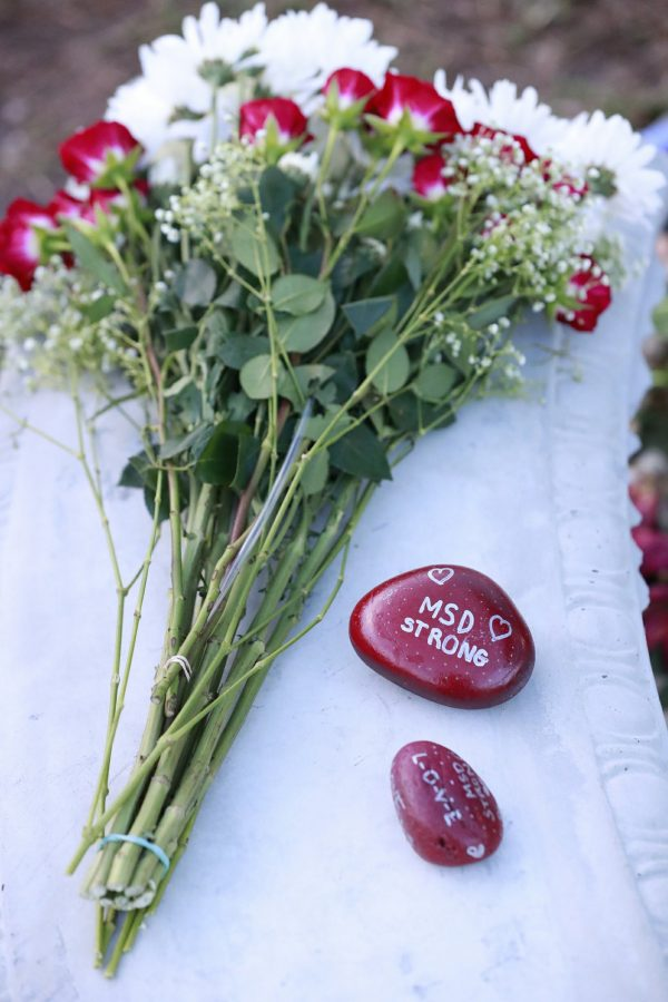 Flowers and stones are shown at a memorial outside Marjory Stoneman Douglas High School