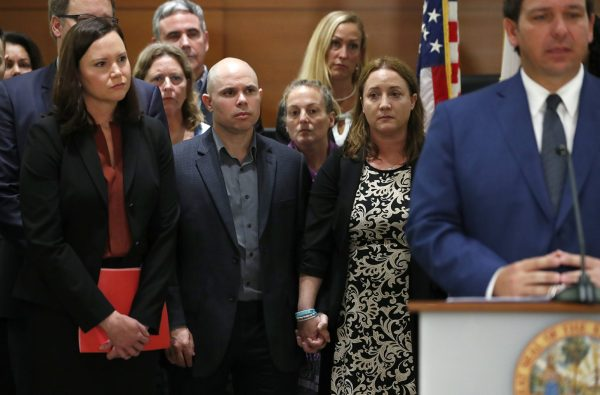 Ilan and Lori Alhadeff, center, the parents of Alyssa Alhadeff, who was killed in the Parkland, Fla., school shooting, hold hands