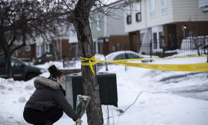Local resident Jennifer Fuller places flowers at the scene outside of a house where a young girl was found dead in Brampton, Ont. on Friday, February 15, 2019. (The Canadian Press/Andrew Ryan)