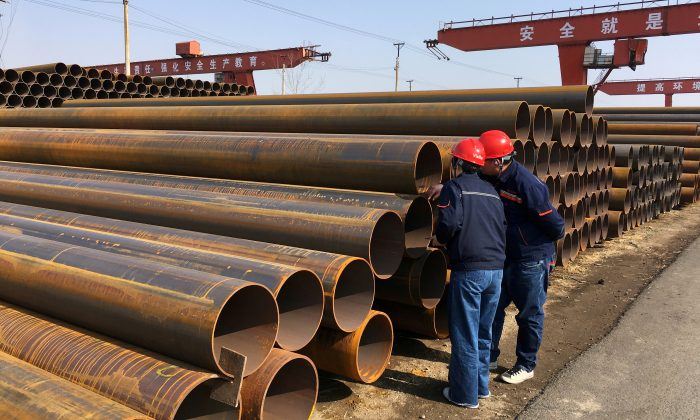 Workers inspect steel pipes at a steel mill of Hebei Huayang Steel Pipe Co Ltd in Cangzhou, Hebei Province, China on March 19, 2018. (Muyu Xu/Reuters)