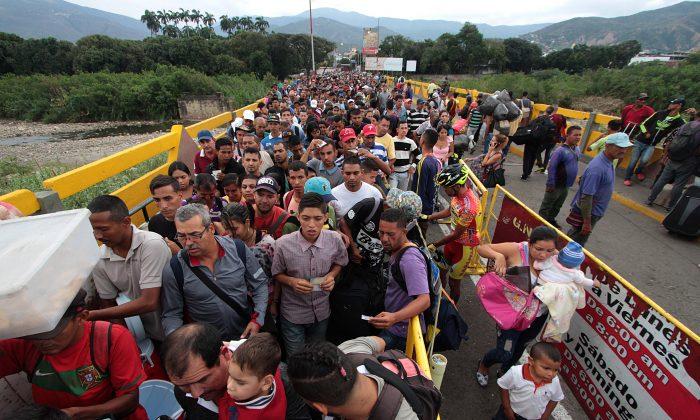 Venezuelan citizens cross the Simon Bolivar international bridge from San Antonio del Tachira in Venezuela to Norte de Santander province of Colombia on February 10, 2018. (GEORGE CASTELLANOS/AFP/Getty Images)