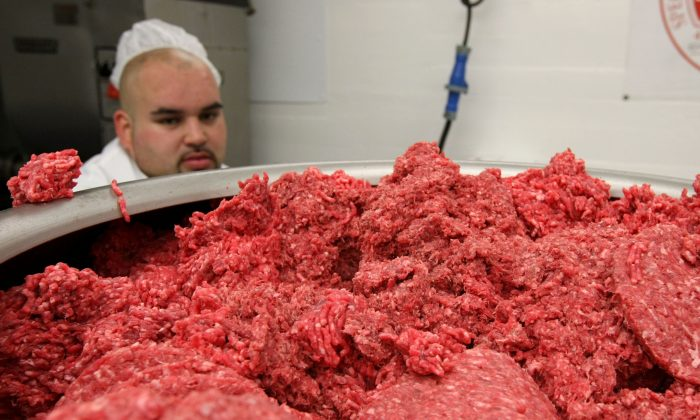 File photo showing a worker at a meat packing facility monitoring ground beef as it passes through a machine that makes hamburger patties. (Justin Sullivan/Getty Images)
