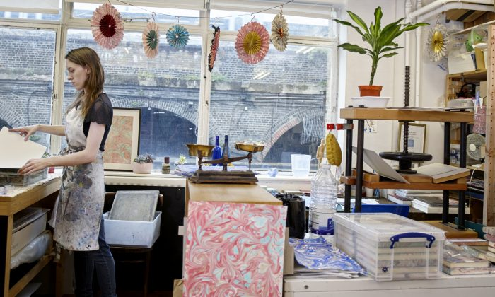 Lucy McGrath in her paper-marbling studio. Paper marbling is a critically endangered craft in the UK. (Rankin Studios)