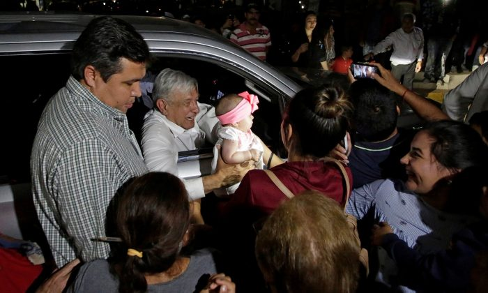 Mexico's President Andres Manuel Lopez Obrador holds a baby while leaving an event in Badiraguato, in the Mexican state of Sinaloa, Mexico, on Feb. 15, 2019. (Daniel Becerril/Reuters)