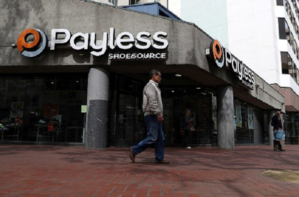 A pedestrian walks by a Payless Shoe Source store in San Francisco