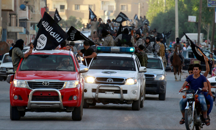 ISIS terrorists waving flags, travel in vehicles as they take part in a military parade along the streets of Syria's northern Raqqa Province June 30, 2014.  (Reuters)