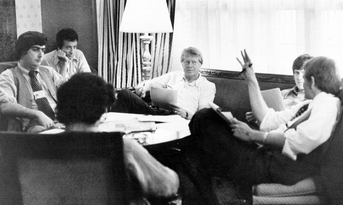Jimmy Carter, center, meets with his staff, from back left, Pat Caddell, Jerry Rafshoon, his son, Chip and Jody Powell, and front left, Pat Anderson, at the Americana Hotel in New York on July 14, 1976. (AP Photo/Pool, File)