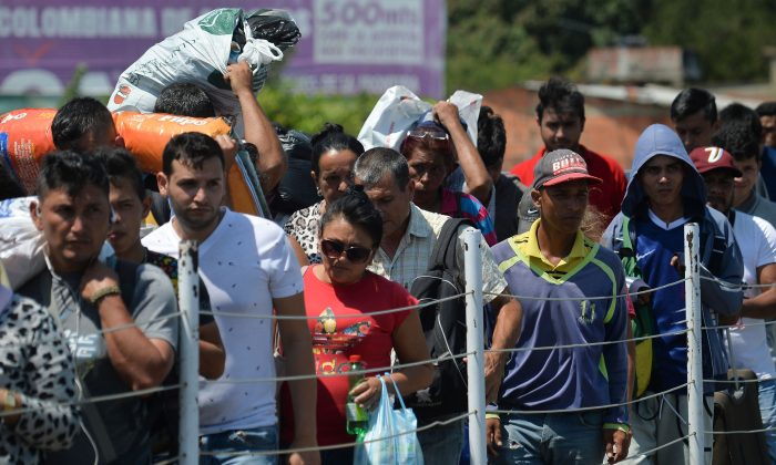 People cross the Simon Bolivar International bridge from Cucuta, Colombia to San Antonio, Tachira, Venezuela, on Feb. 16, 2019. Venezuelan opposition leader Juan Guaido on Feb. 16 called for nationwide protests next week to support volunteers planning to travel to the border with Colombia to bring in US humanitarian aid. (Luis Robayo/AFP/Getty Images)