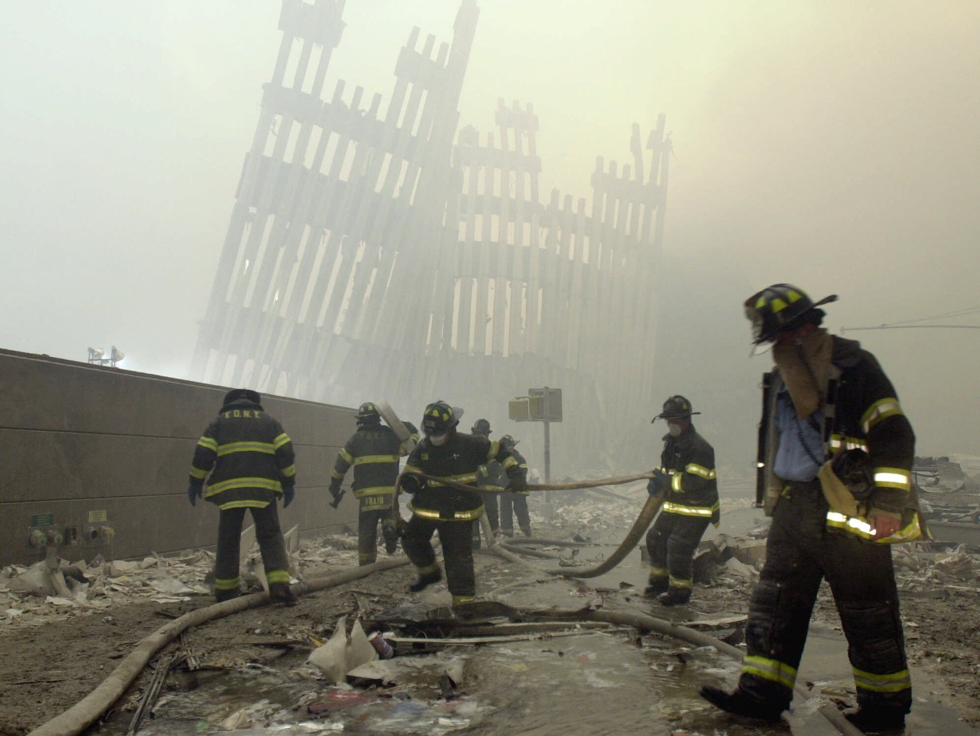 New York City firefighters work amid debris on Cortlandt St. after the terrorist attacks on Sept. 11, 2001