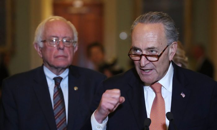 Senate Minority Leader Charles Schumer (D-N.Y.) (R) is flanked by Sen. Bernie Sanders (I-Vt.) while speaking to the media on Capitol Hill on May 23, 2017. (Mark Wilson/Getty Images)