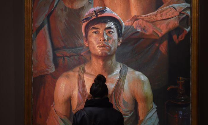 """A visitor looks at a painting of a worker at an exhibition titled """"Image of People"""" in Beijing on November 23, 2015. (GREG BAKER/AFP/Getty Images)"""