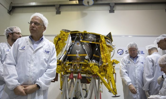 "Technicians stand next to the SpaceIL lunar module, an unmanned spacecraft, is on display in a special ""clean room"" where the spacecraft is being developed, during a press tour of their facility near Tel Aviv, Israel. SpaceIL and state-owned Israel Aerospace Industries told a news conference that the landing craft will take off from Florida, to its weekslong voyage to the moon. (AP Photo/Ariel Schalit, File)"