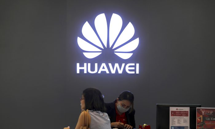 A woman sits next to a salesperson at a Huawei shop in Bangkok, Thailand on Jan. 30. (Athit Perawongmetha/Reuters)