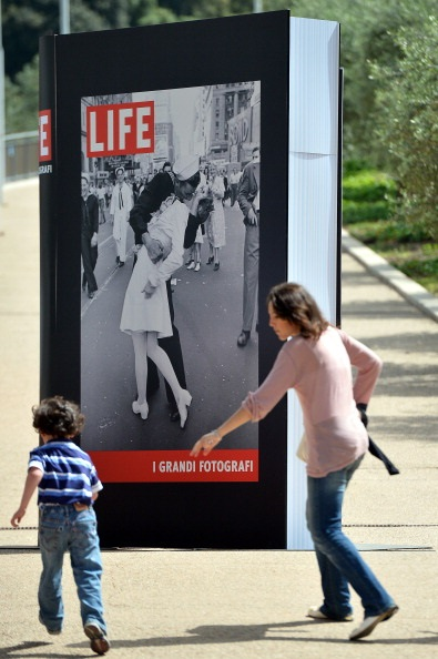 "A People pass by a poster announcing the ""Life. I grandi fotografi"" (Life. The great photographers) exhibition with ""VJ Day a Times Square,"