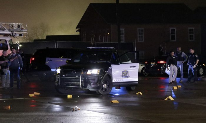 Evidence markers are placed in the Dollar General parking lot, located in the 1100 block of Opelika Road in Auburn, Ala., on Friday, Feb. 15. (Emily Enfinger/Opelika-Auburn News via AP)