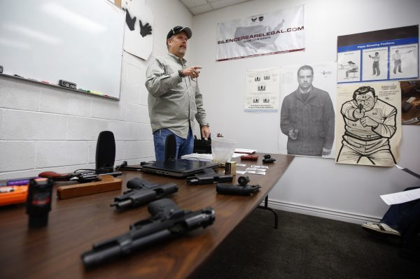 A gun instructor teaches a packed class