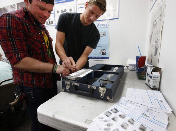 An unidentified person has his fingerprints taken