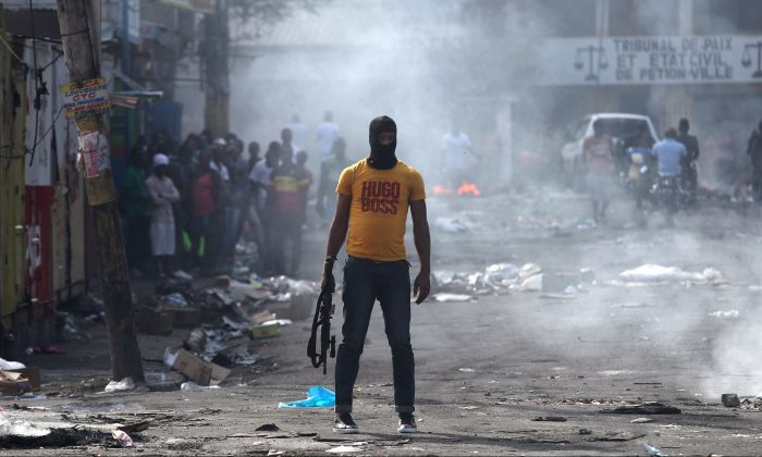 A man holds a weapon next to burning barricades during anti-government protests in Port-au-Prince, Haiti, Feb. 17, 2019. (Ivan Alvarado/Reuters)