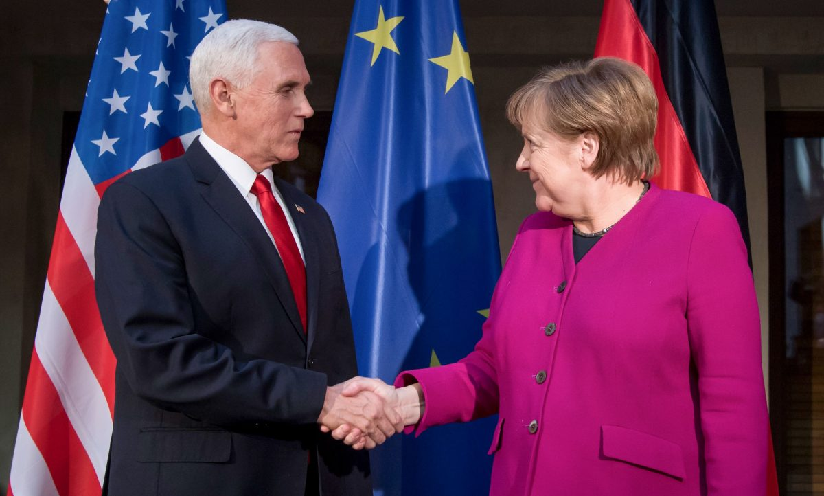 German Chancellor Angela Merkel (R) and US Vice President Mike Pence shake hands at a photo call during the 55th Munich Security Conference in Munich, southern Germany
