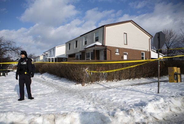 Police monitor the scene outside of a house