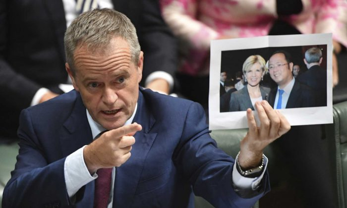 Australian Opposition Leader Bill Shorten holds a photograph of Australian Foreign Minister Julie Bishop with Chinese businessman Huang Xiangmo during House of Representatives Question Time at Parliament House in Canberra, June 14, 2017. (AAP Image/Lukas Coch)