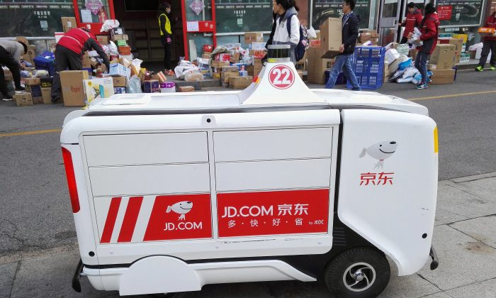 A JD.com driverless delivery robot is seen in front of parcels outside a JD.com logistics station at Renmin University of China a day after the Singles Day online shopping festival, in Beijing on Nov. 12, 2018. (Liu Hongsheng/Qianlong.com via Reuters)
