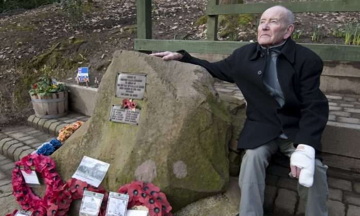 Tony Foulds sits next to a memorial honouring 10 U.S. airmen who died in a 1944 plane crash in Endcliffe Park, Sheffield, England, on Feb. 13, 2019. (Rui Vieira/AP Photo)