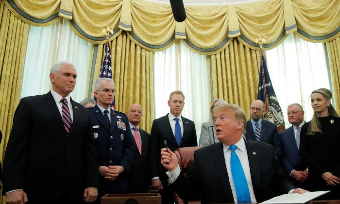 """U.S. President Donald Trump looks to Vice President Mike Pence as he participates in a signing ceremony of """"Space Policy Directive 4,"""" to establish a Space Force as the sixth branch of the Armed Forces, in the Oval Office at the White House in Washington, U.S., on Feb. 19, 2019. (Jim Young/REUTERS)"""