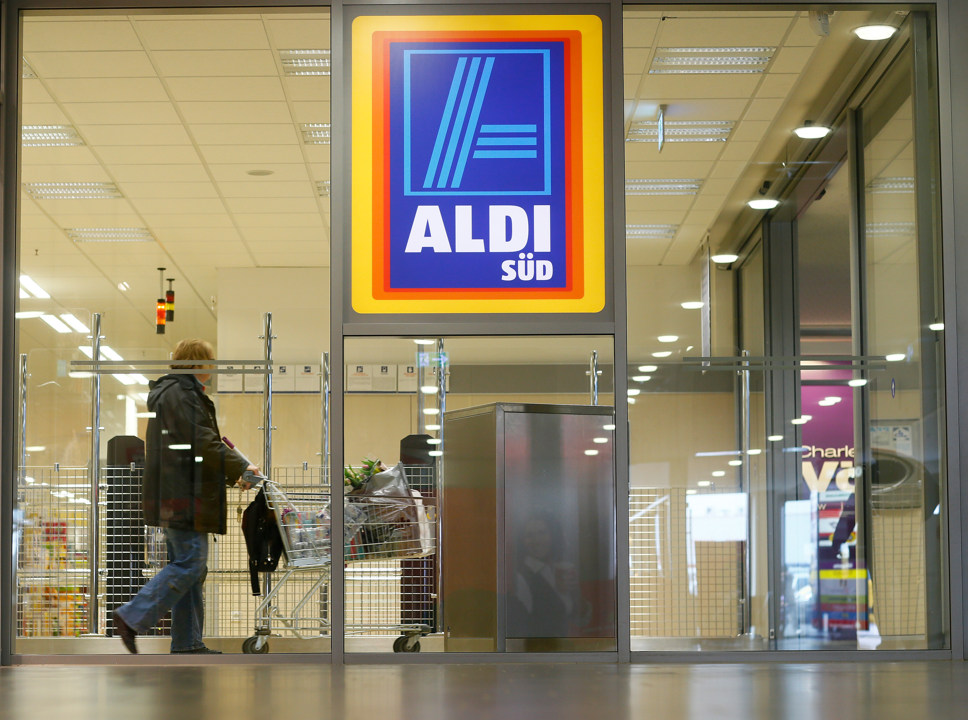 A shopper pushes a shopping cart in an Aldi