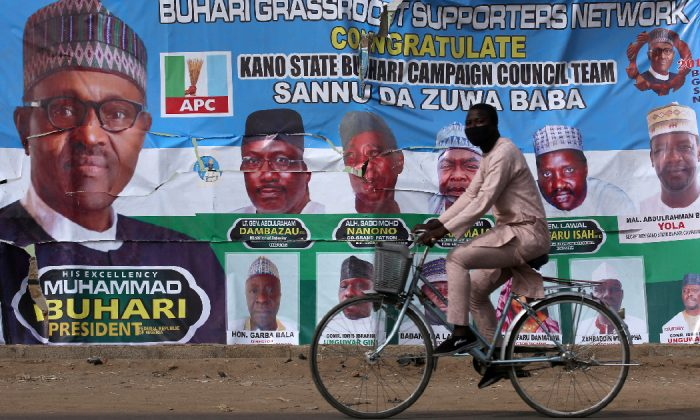 A cyclist drives pasts a campaign poster for President Muhammadu Buhari in a street after the postponement of the presidential election in Kano, Nigeria Feb. 17, 2019. (Luc Gnago/Reuters)