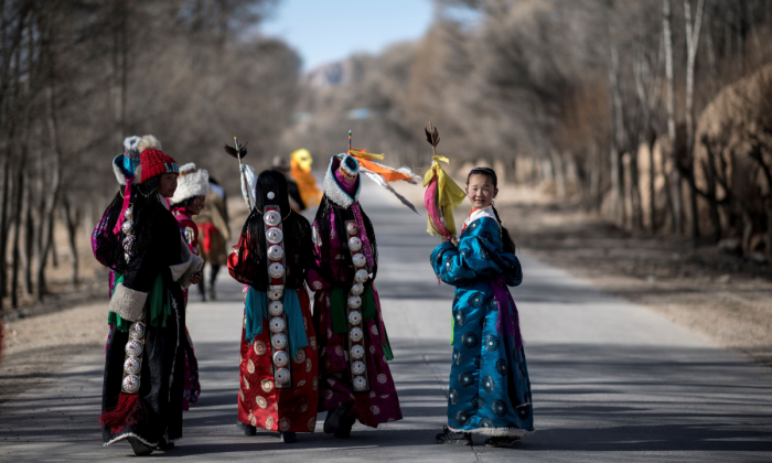 Girls dressed in traditional Tibetan costumes walking down a road after a festival to mark the Tibetan New Year celebrations in the village of Douhoulou, some 50 kms south of Guide on the Qinghai-Tibet Plateau on Feb. 25, 2018. (JOHANNES EISELE/AFP/Getty Images)