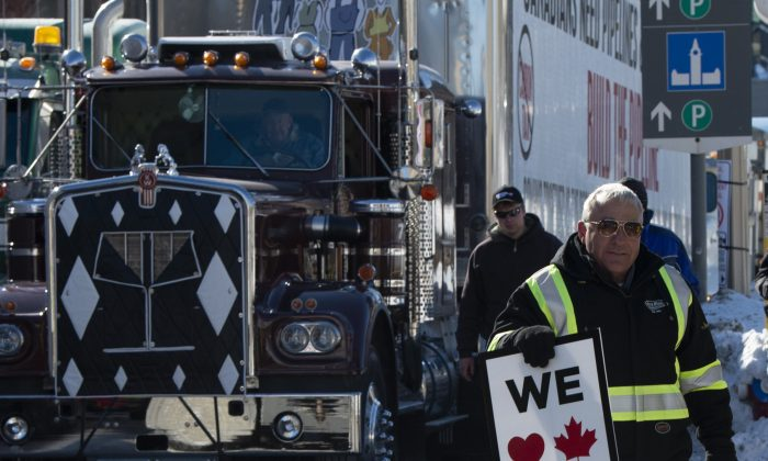 A pro-oil protester stands near convoy vehicles in front of Parliament Hill in Ottawa, Feb. 19, 2019. (The Canadian Press/Adrian Wyld)