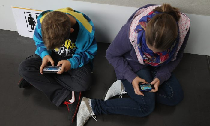 Children play video games on smartphones while attending a public event on Sept. 22, 2012 in Ruesselsheim, Germany. (Sean Gallup/Getty Images)