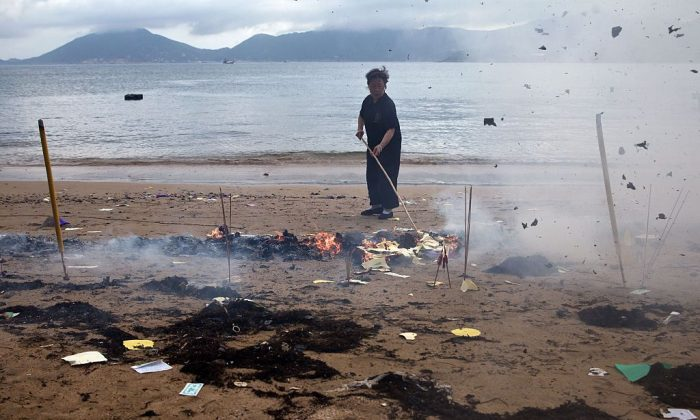 A worker burns offerings on a beach at Joss House temple to celebrate the Tin Hau festival in Hong Kong on May 10, 2015. (Dale de la Rey/AFP/Getty Images)