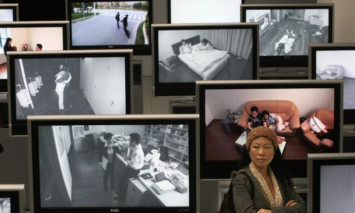A Chinese woman stands next to videos showing domestic violence and marriage breakdowns at an exhibition in Shanghai, on March 15, 2007. (Mark Ralston/AFP/Getty Images)