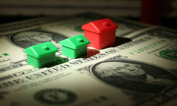 File photo of miniature houses from a Monopoly board game next to American dollar notes. Under Modern Monetary Theory, government has the monopoly on money creation and can use it to take control of the private sector. (Christopher Furlong/Getty Images)